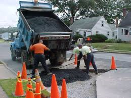 Public Works Employees Fill a Pothole With Fresh Asphalt from a Dump Truck