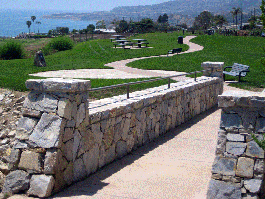 Stone bridge leading to grass area and trail with benches, tables and view of ocean